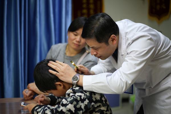 检查患者头部白斑